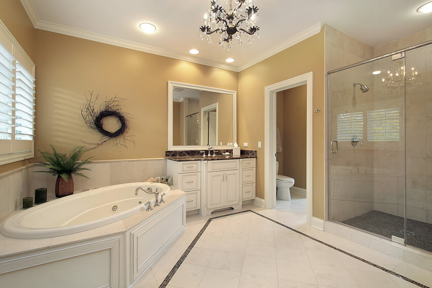 Master bath white flooring yellow paint glass chandelier