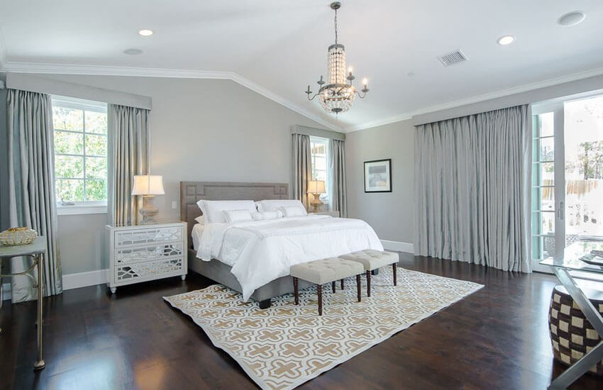 With walls covering in silver hue, and a stylish chandelier hanging overhead, this master bedroom with silver wall covering and decor with walnut floors is airy and bright, though accented with dark walnut flooring surface