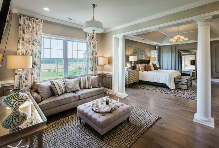 The sweeping outside views offer by the wide windows add energy and vitality while enhancing the warmth of the hardwood floors in this master bedroom with warm hardwood floors and sitting room