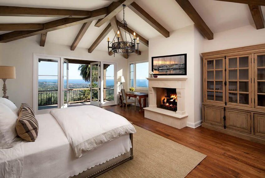 The rich texture of the red oak hardwood floors, and the elegance of the fireplace and vintage chandelier contribute to the cozy feeling of this mediterreanean style master bedroom red oak flooring chandelier and balcony views