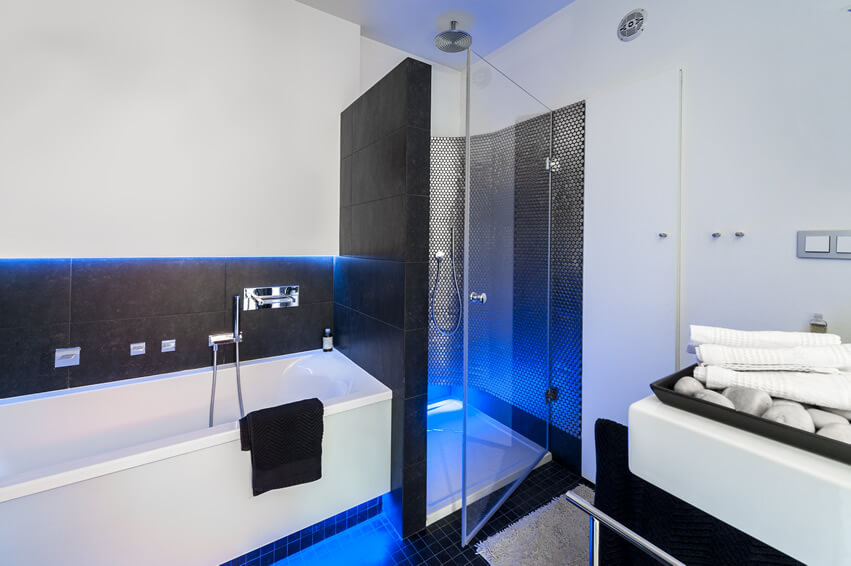 The modern black white bathroom neon blue lights enhance an ocean view illusion, while the black checkered mosaic floor tiles and clean line porcelain tub are a perfect color combination for a beach side home design