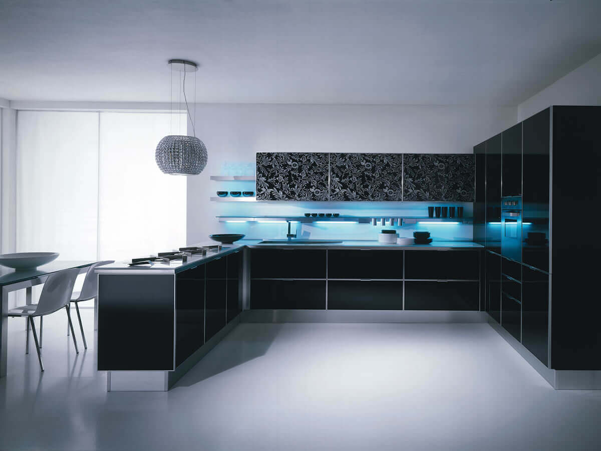 It is easy to come up with a common combinations of white and black when planning a modern kitchen design, but do dare to dream of the unexpected. The backlit blue luminous backsplash keeps the focus on the elegance of the black cabinets and countertops