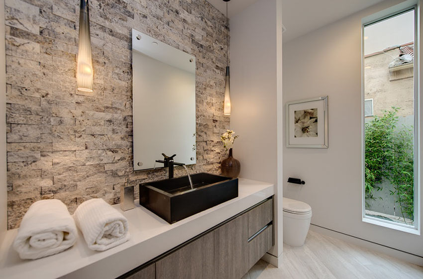The designer of this modern master bathroom with luxury pendant lights gives it a big dose of glamor with exposed brick accent wall, a large antique square shaped mirror, a big black wood sink, and two beautiful hanging pendants