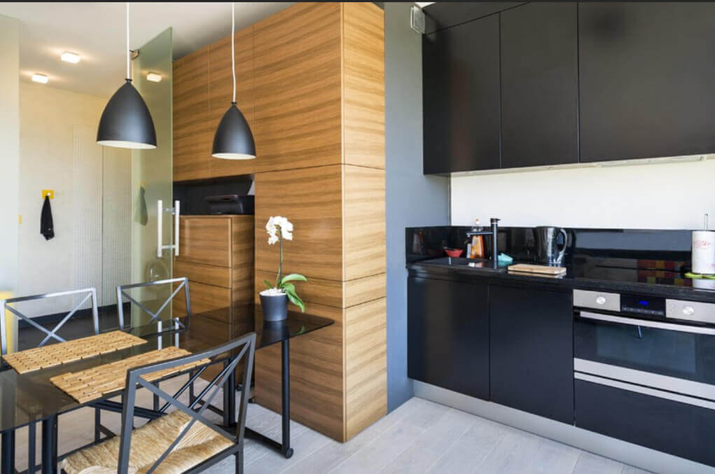 Unique modern small kitchen design in a natural wood and black cabinet! The black industrial–style hanging lamps bring together the look while the light wood floors carry the modern feel to the flooring