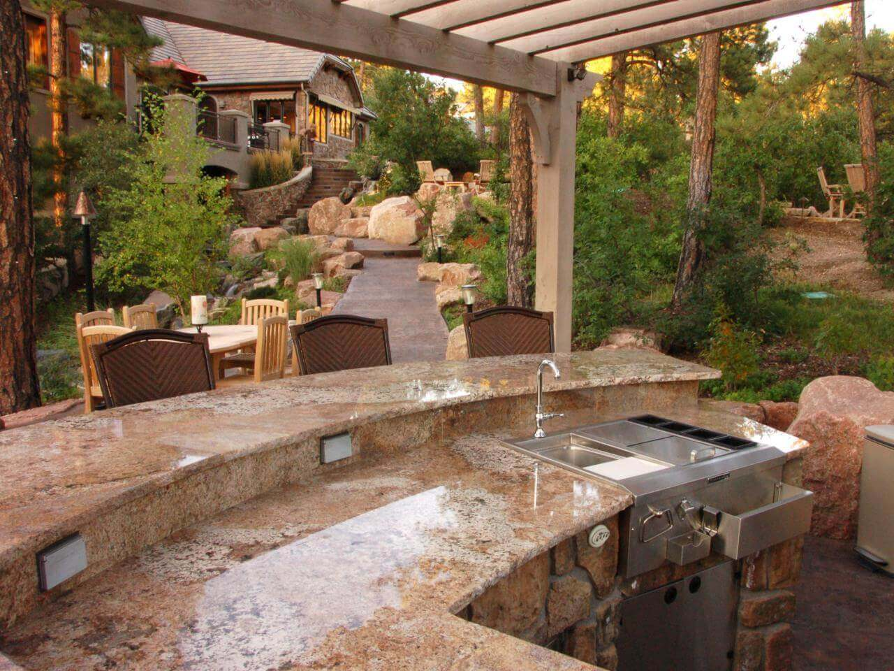 Give new life to your backyard barbecues this summer with outdoor kitchen decorating ideas. Marble countertops and stainless steel appliances give this outdoor kitchen idea a modern feel. Herb garden fill with trees and flowers give the space a natural feel