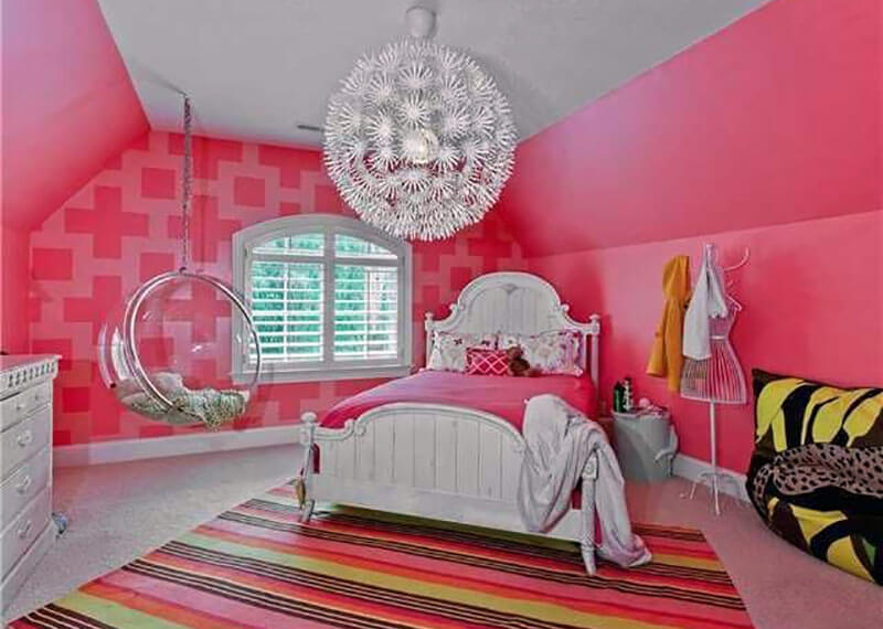 The round see through swinging bubble chair is an excellent addition to this modern style pink girls bedroom with round swinging chair with clear sides. The room also features a large hanging lamp with fins which lights up the entire space