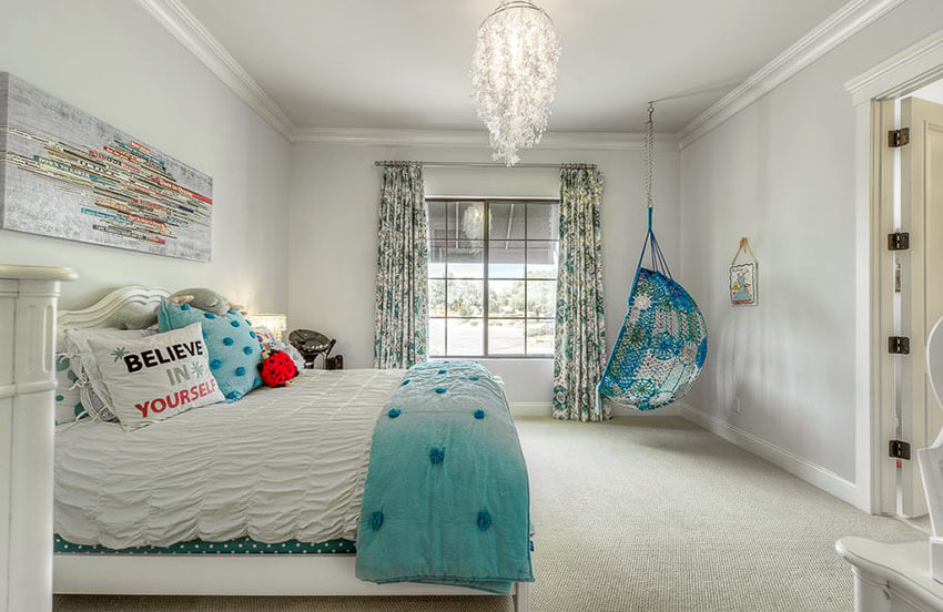 This pretty girls bedroom with aqua color hanging chair and feather chandelier features a feather chandelier and a painting mural. Knitted up in aqua color with floral patterns, the swinging chair is hung next to a large window