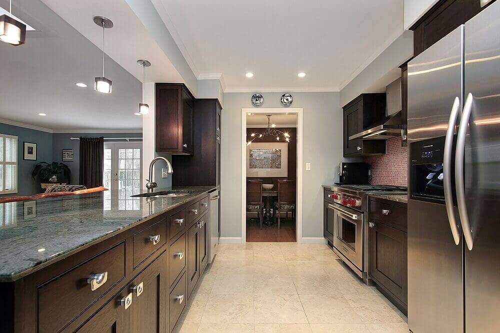 In this rectangular kitchen design, dark wood cabinets are paired with marble countertops to give the space a modern look. Large stainless steel appliances and light tiled flooring further accent the feel of the kitchen