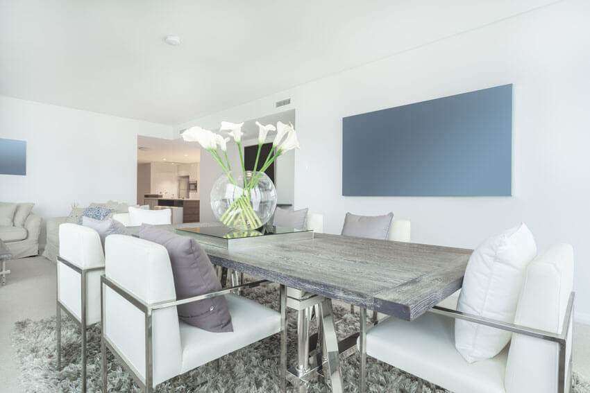 silver dining table and chairs with white cushions