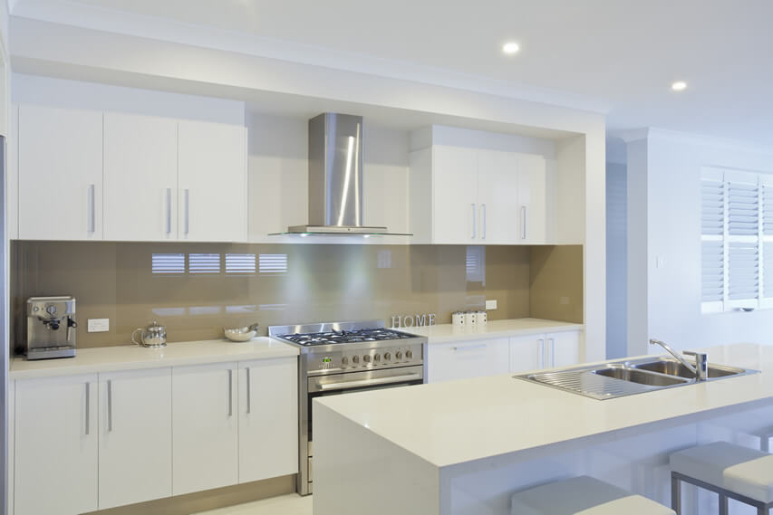 This sleek white small kitchen design is an epitome of clean, modern design. The design incorporates a warm gray and simple white palette with little ornamentation. It features a simple island bar counter with white solid–surface countertops and laminated cabinets