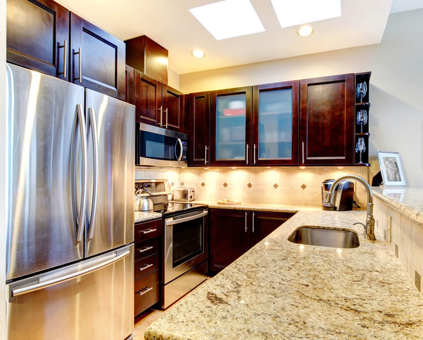 With its miniature nature, this small galley kitchen design granite stainless appliances is able to nicely fit a small bar ledge and a French door refrigerator into U–shaped design. The white color of the walls and backsplash help make the space appear bigger