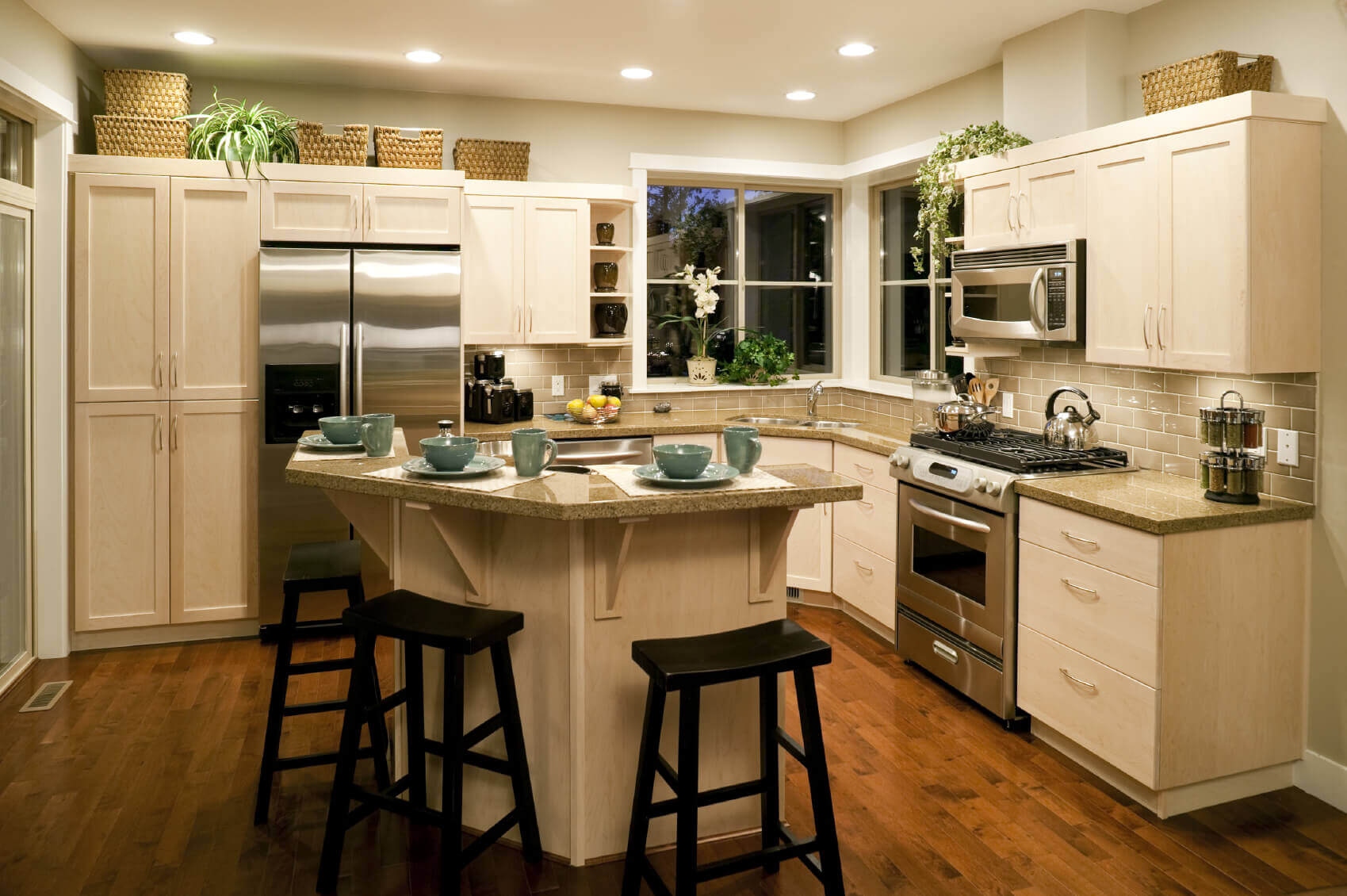 The kitchen island in this small kitchen design with island was designed to include a breakfast section that helps divide attention between the cooking area and the island. A line of beautiful barstools provides seating for friends, family, and guests
