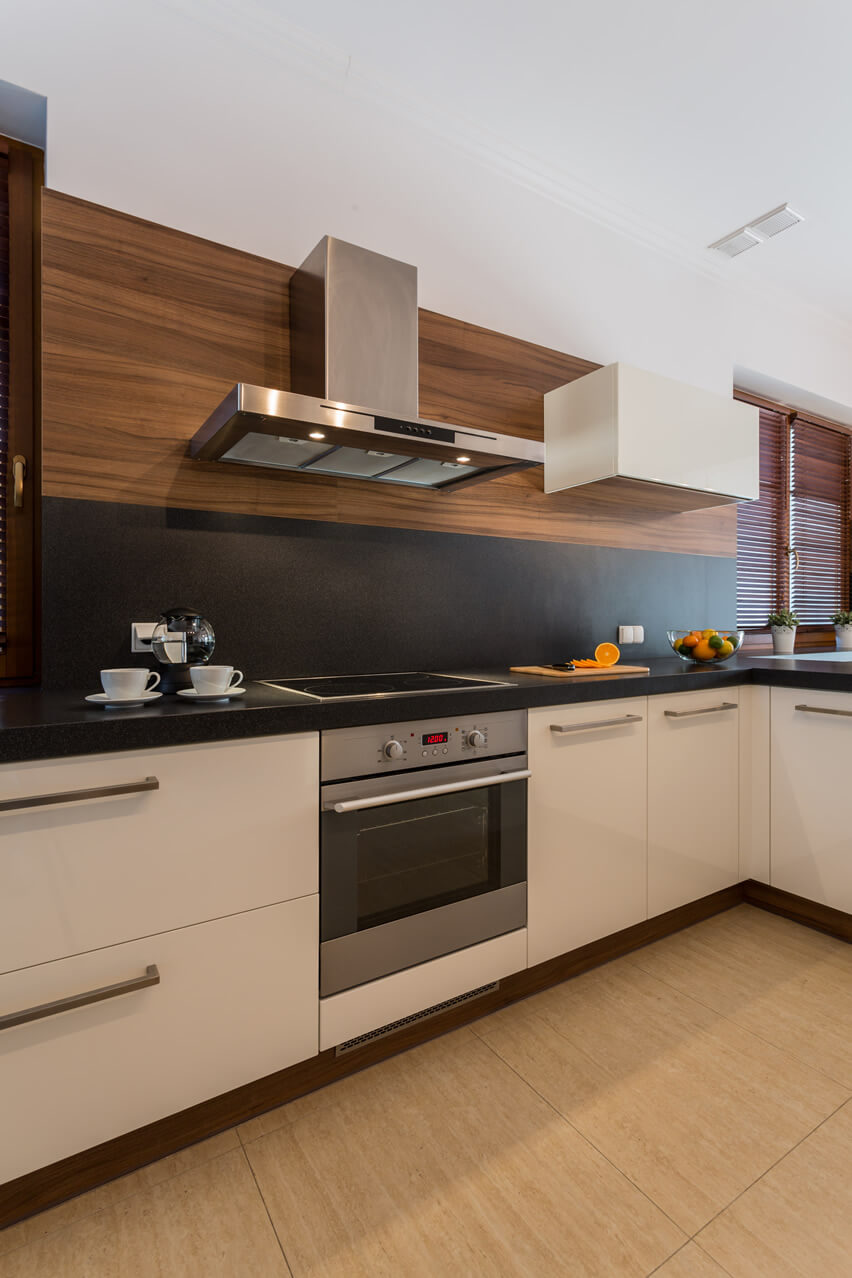 The defining feature of this small kitchen modern home white cabinets black backsplash is its beautiful combination of black solid surface and light walnut wood panel for its splashboard. The cabinets in white laminates are kept simple with stainless steel hardware