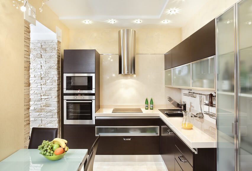 This small modern kitchen design uses a simple l–shape layout with refreshingly light yellow walls and crisp white ceiling to help make the space seem bigger. The kitchen features dark wood cabinets with low–profile stainless steel appliances
