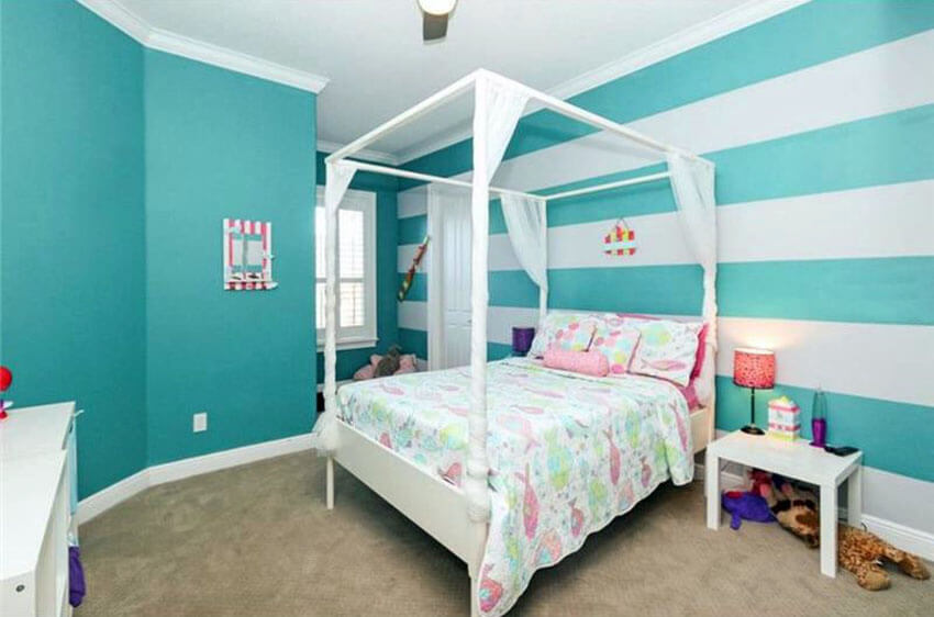 This teal and white striped wall bedroom design with four post bed looks comfortable enough for children to live and play in. The four poster bed is in plain white with sheer curtains and matching colorful green and pink pillows and bed sheets