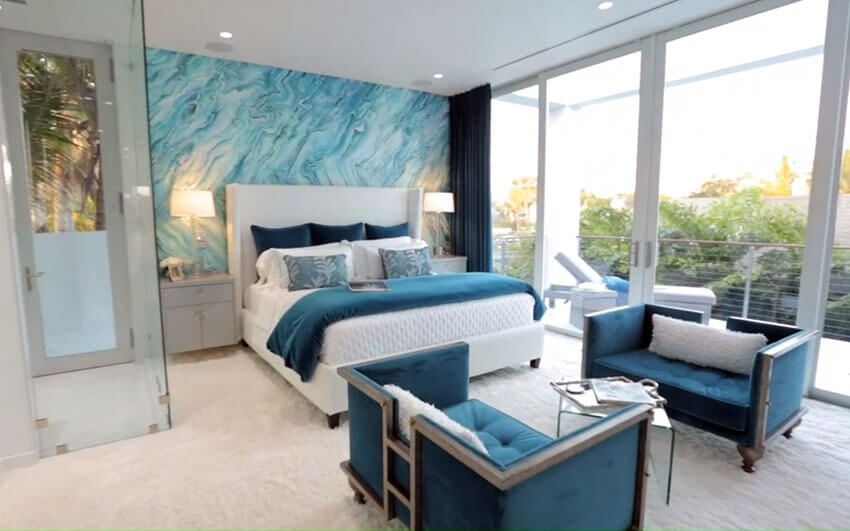 This teal bedroom with accent wall sitting area furniture and balcony looks beautiful and inviting. The large abstract accent wall that blends a blue, white, and green color pattern makes a big impression