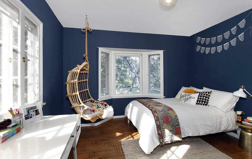 This teenager bedroom with hanging rattan chair and blue walls made use of modern style rattan material to create a woven swinging chair. The hanging rope combines nicely with the rattan material to accent the white window frames and the room's dark blue walls