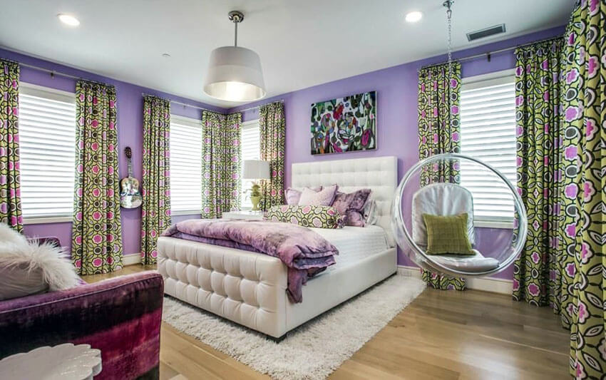 Fitted with geometric patterned green curtains, this teens bedroom with purple walls shag carpet and see through swinging bubble chair with cushions was brought to live by its modern shade of purple. It features a contemporary style shade lamp hanging along with the swing bubble chair