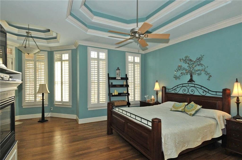 Traditional Bedroom with Teal Painted Walls Wood Flooring and White Molding