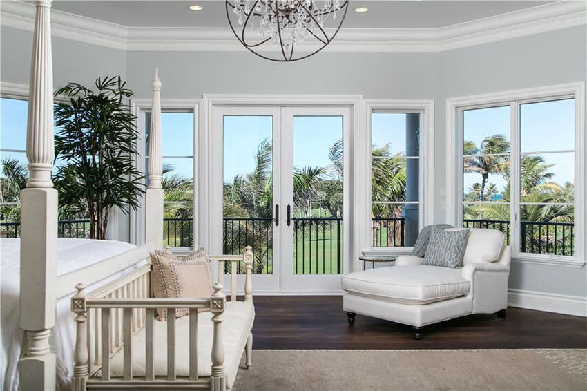 Instead of relying on prints or framed artwork, this traditional master bedroom walnut hardwood floors and golf course views use oversized floral plant and plenty of large windows to not only add personality, but to further enhance the golf course views