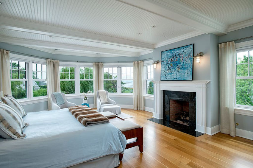 Overly sombre interior designs can sometimes result from the misuse of wood flooring surfaces, but the smart use of lots of white appeals and generous windows add vitality and energy to this traditional master bedroom with light wood floors