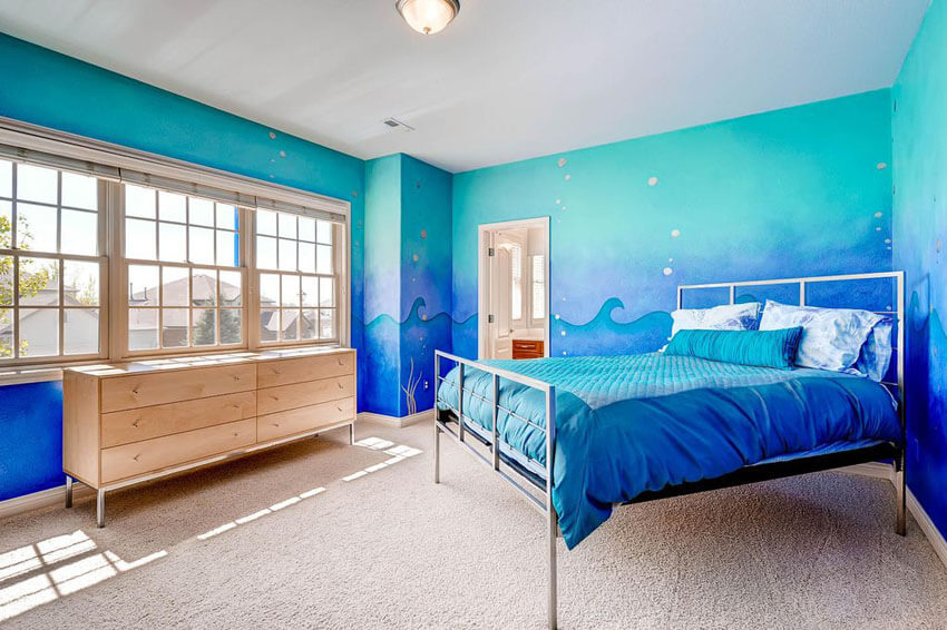 This bright, tropical bedroom with blue painted walls with wave art design has simple furniture with its steel framed bed, maple wood drawers, off–white carpet, and white double hung windows. The wave art design walls that perfectly match with the bedsheets and pillows is the room's most unique element