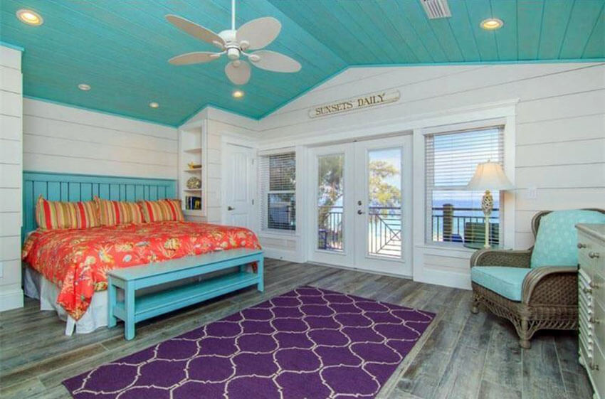 The eye–catching elements of this tropical cottage bedroom with teal color ceiling and teal bed frame are its sloping teal colored plank ceiling and white plank walls. The purple arabesque patterned throw rug at the foot of the bed and the red–orange floral, pinstriped bedsheets nicely contrast the overall hue of the space