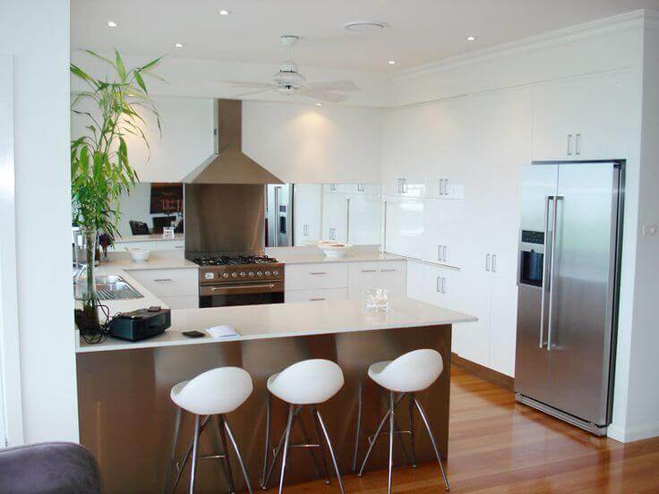 Thoroughly white u–shaped kitchen design features natural wood flooring with crisp white cabinetry and fine wood island with contrasting white counter top. The breakfast bar features exquisite white barstools that further enhance the white feel of the space