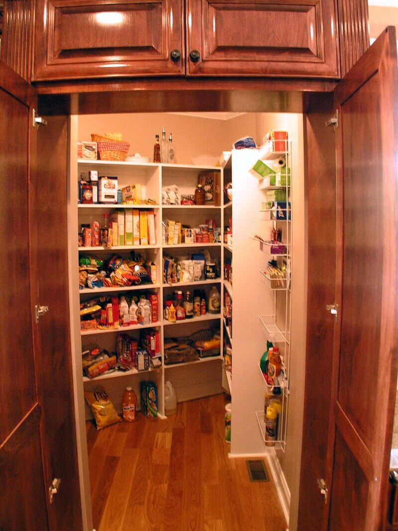 One major benefit of a walk–in pantry is having all your groceries well organized in a not–too far handy distance behind a closed door. This walk–in kitchen pantry tucks away behind a dark wood cupboard into the design