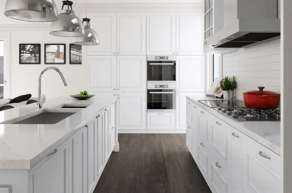 The aluminum appliances and large stainless steel pendant lighting fixtures hang above the island create a striking visual contrast against the crisp white cabinetries and the clean white island. Dark wood flooring balances out the all white feel of the white kitchen design
