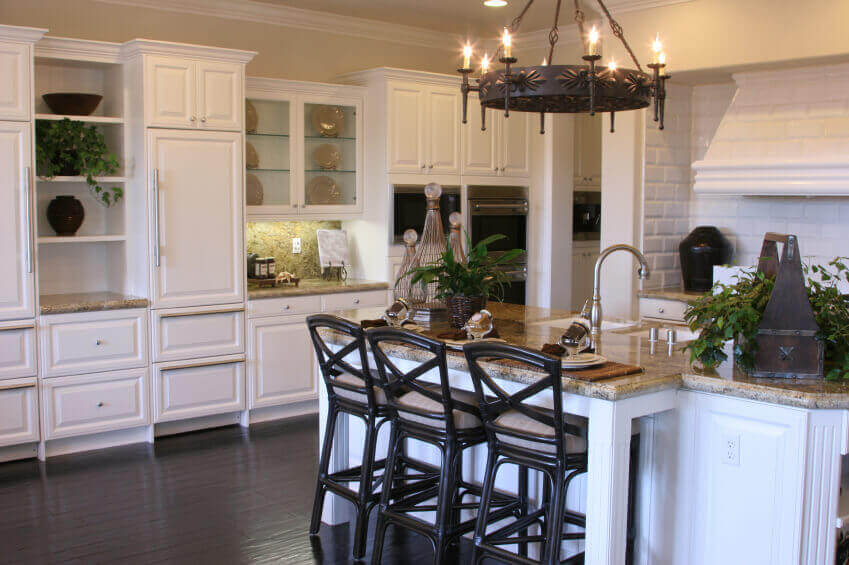 This white kitchen has a fine dark wood flooring that meshes perfectly with the striking black color in the bar chairs. The stone cream colored countertops give the beautiful white space a pleasant contrast