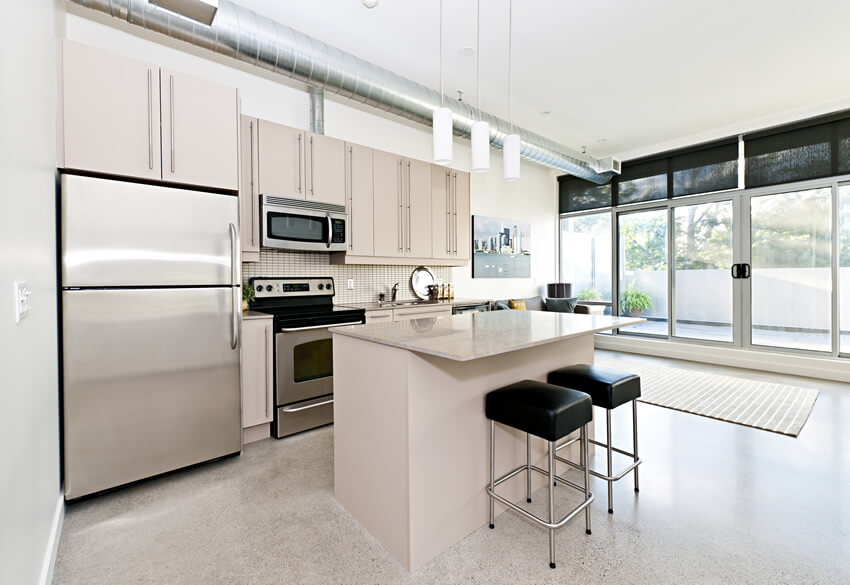 As well as its choice of colors and finishes, the raw and industrial appeal of this white small size kitchen with island barstools brings forth its charm. It incorporates light cream colored cabinets topped with matching cream granite countertop