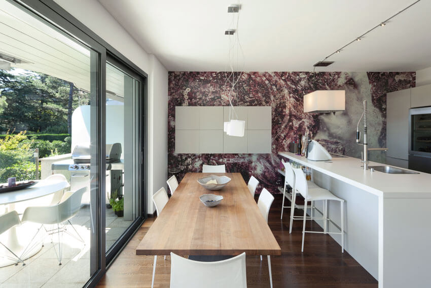 wood dining table next to white modern kitchen