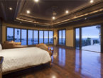 luxury master bedroom with dark oak flooring and ocean views