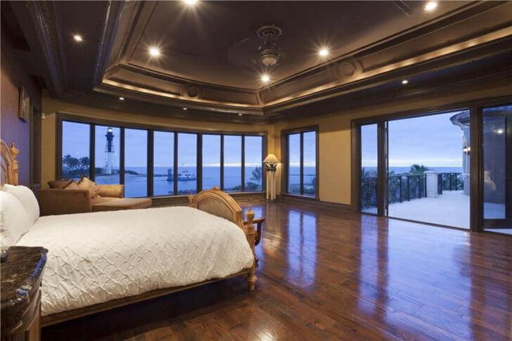 luxury master bedroom with dark oak flooring and ocean views