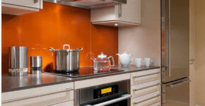 Modern kitchen with orange walls and chrome appliances