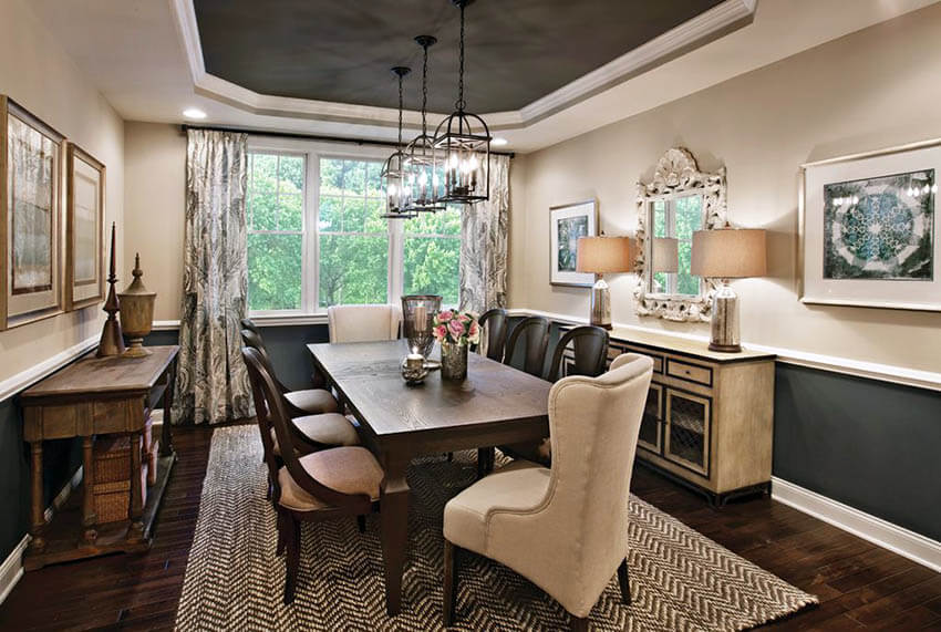 dining room with dark tray ceiling and craftsman style metal pendant lights