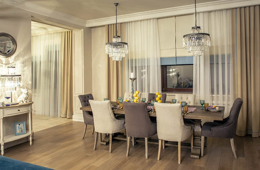 dining room with two crystal chandeliers and matching table lamp and mirror