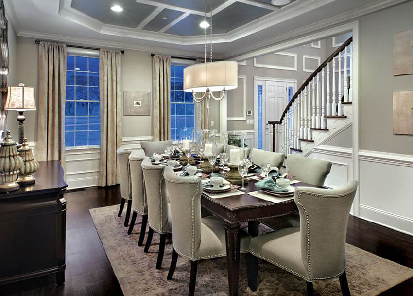 dining room with warm lighting linen shade chandelier table lamp and recessed lights